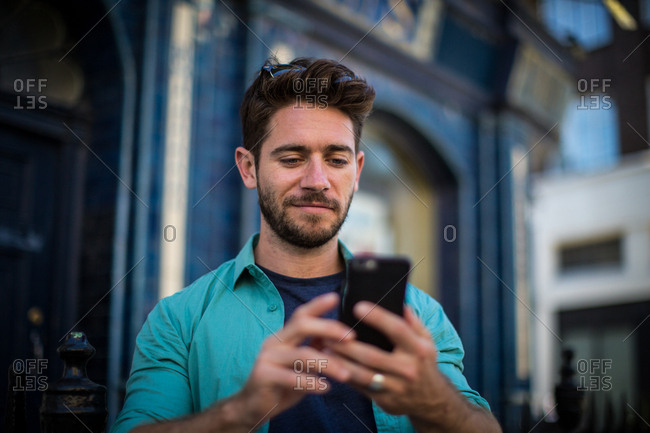 Young adult standing outside London pub using smartphone