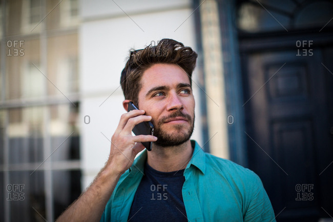 Young adult leaving his home on smartphone