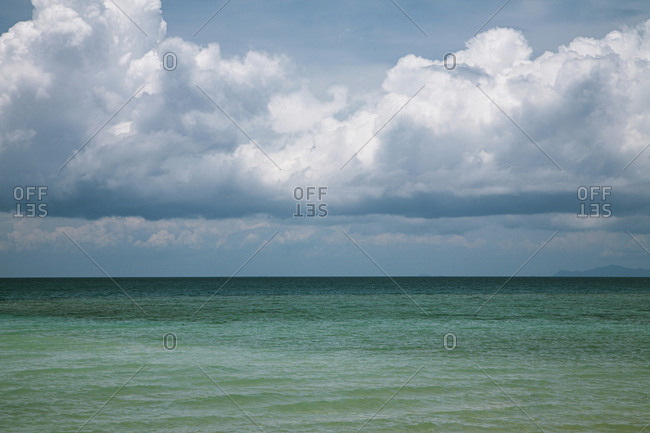 Picturesque view of vast tranquil ocean of different colors from turquoise to deep blue on cloudy afternoon