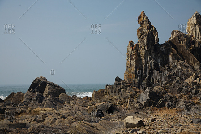 Scenic view of sharp massive rocks against crashing ocean waves and clear blue sky, Goa, India