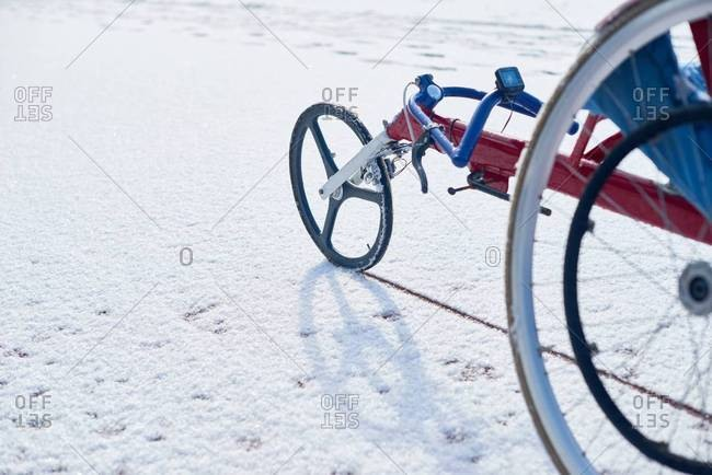Close-up view of modern racing wheelchair standing outdoors on track covered with snow