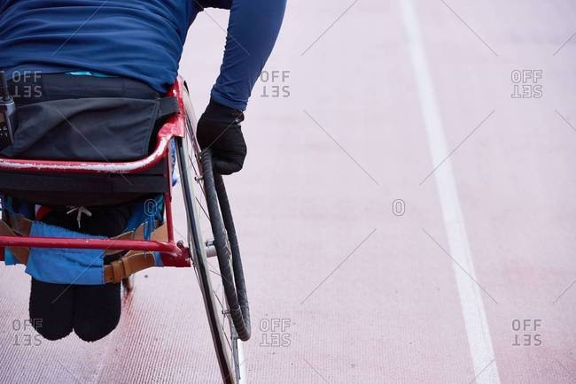 Preparing for Paralympics. Rear view of physically impaired athlete moving in racing wheelchair on track