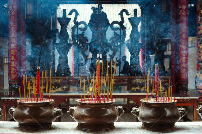 Feng Shui incense sticks burning in brown ceramic pots in Asian temple