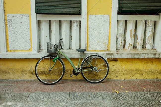 Green retro bike with basket standing on pavement against white and yellow old building with shutters on windows