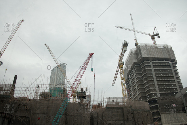 New building project. Low angle view of modern business centers being constructed with help of multiple tower cranes on cloudy afternoon