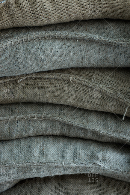 Stack of storage bags. Close-up view of heavy gray linen sacks lying on each other in barn