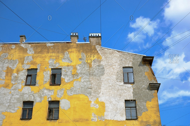 Low angle view of old shabby residential building with peeled yellow paint on blue sky background, Saint Petersburg, Russia