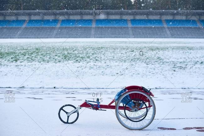 Modern racing wheelchair standing at outdoor track and field stadium covered with snow in gloomy winter afternoon