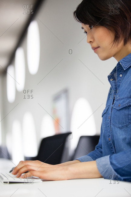 Asian businesswoman typing on a keyboard