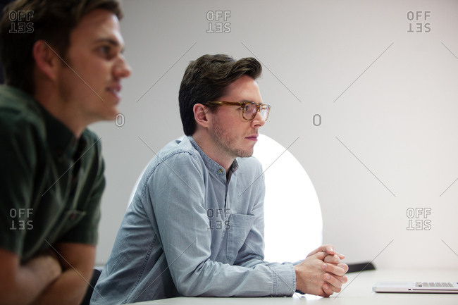 Two businessmen listening in a meeting