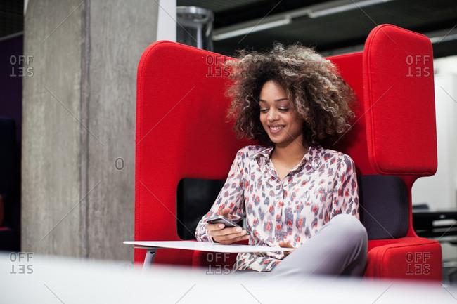 Businesswoman in a pod using smartphone