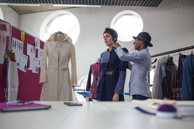 Fashion designer pinning garment on a model