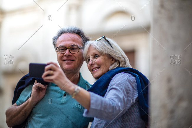 Senior couple on vacation taking a photo at a tourist site