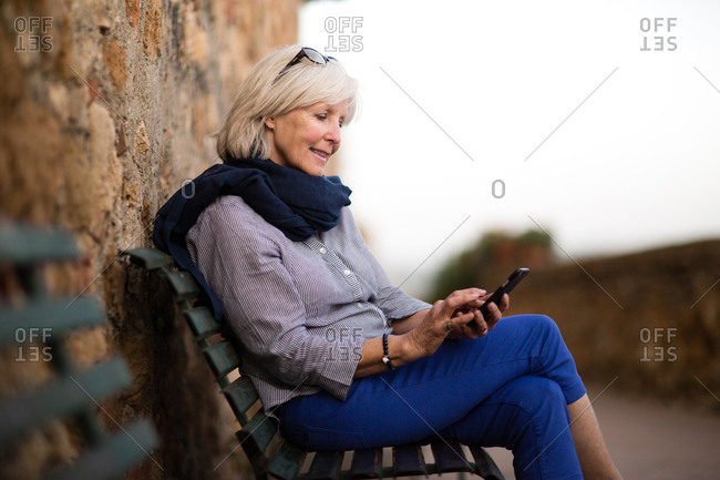 Senior woman relaxing on a bench using smartphone