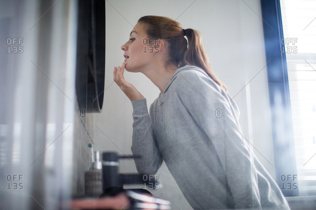 Young adult female putting looking at reflection in bathroom mirror
