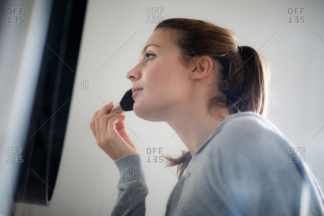 Young adult female putting make-up on in bathroom mirror
