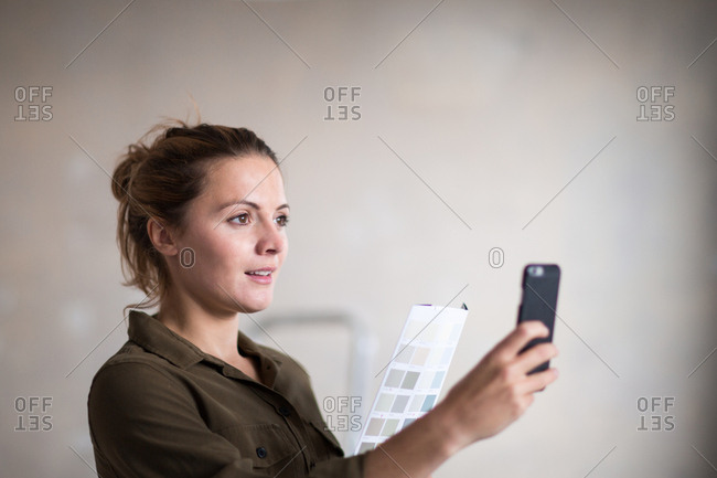 Young adult female choosing paint colors with the help of an app