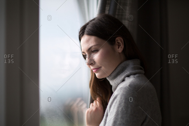 Young adult female looking out of window in winter