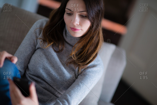 Young adult female using smartphone on sofa