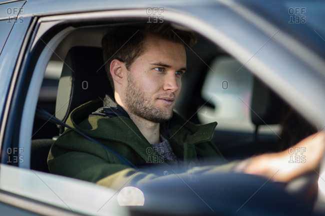Young adult male driving car