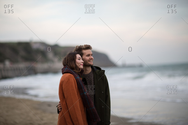 Young adult couple walking on beach