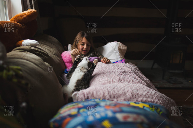 Little girl lying on a couch playing with a cat