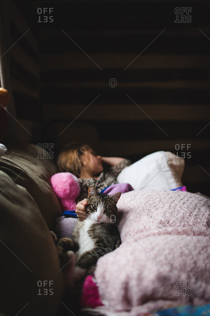 Little girl lying on a sofa rubbing her pet cat