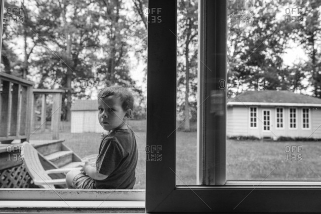Boy sitting on a porch peering in through a screen door