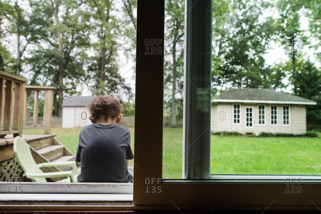 Boy sitting on a back porch in front of a screen door