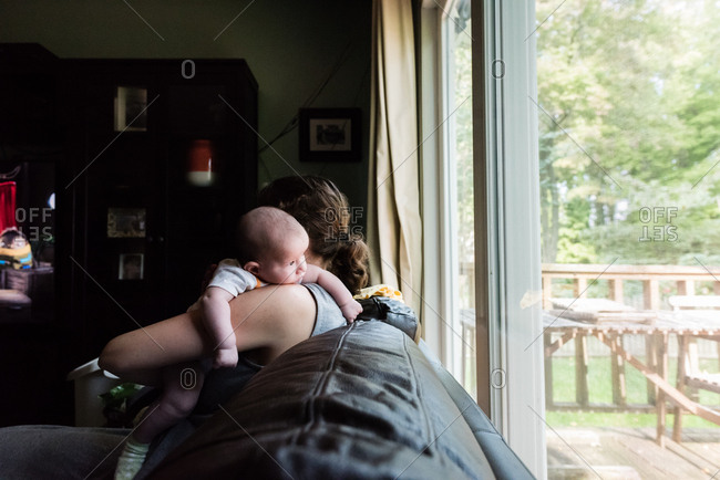 Woman sitting on a couch holding her infant son over her shoulder