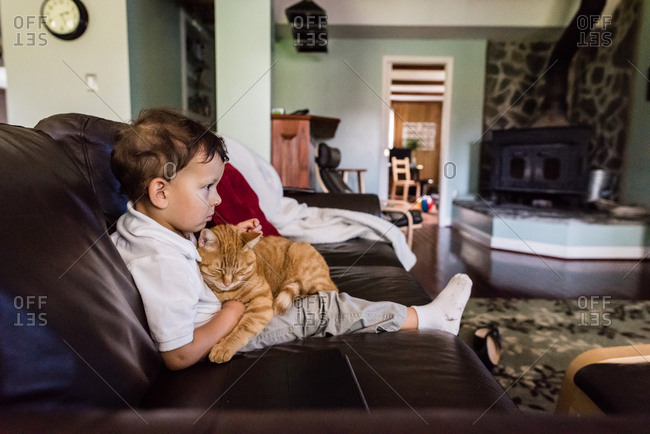 Boy sitting on a sofa with his pet cat in his lap