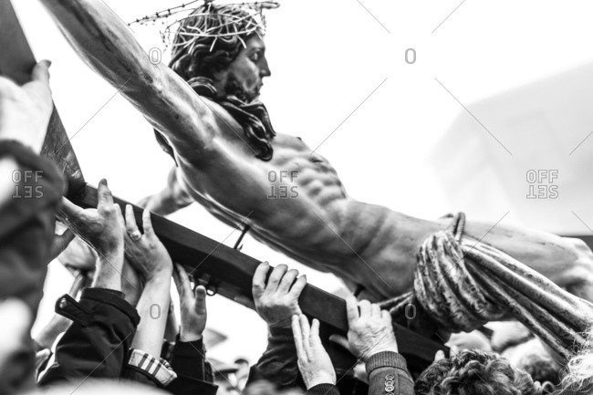 Hands of many people carrying cross with statue of the crucified Christ during Holy Week procession in Sicily