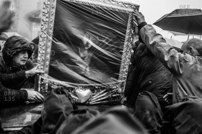 San Marco d'Alunzio, Italy - March 27, 2015: Many people carrying and touching an icon of the Madonna during Holy Week procession in Sicily