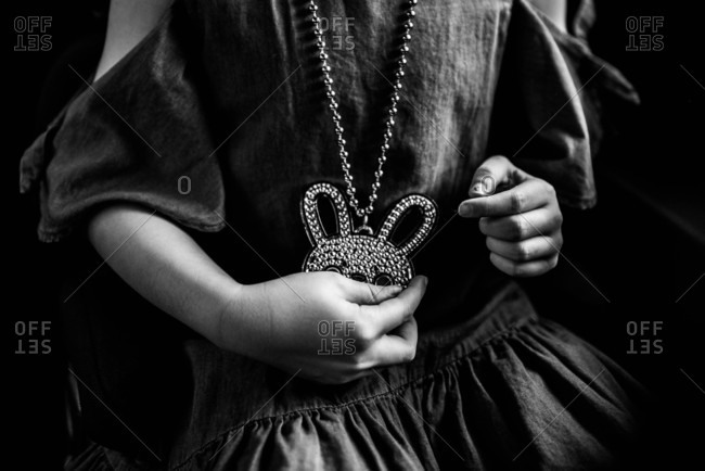Little girl in a dress holding a bejeweled rabbit necklace