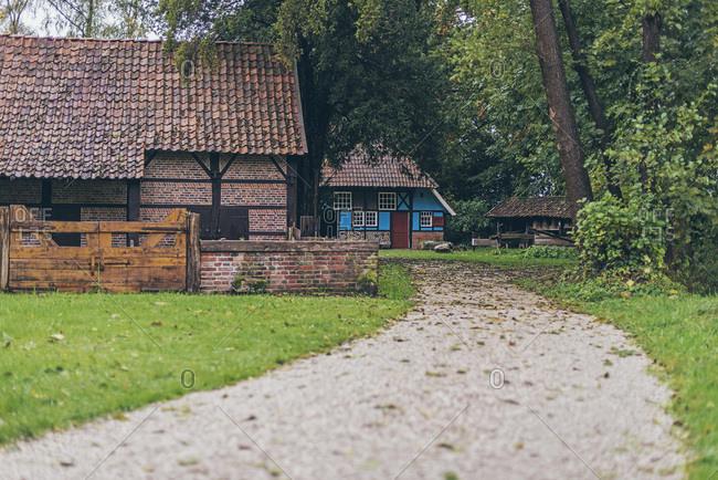 Path in farmyard with antique Dutch farm.