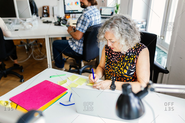 Female editor writing on adhesive note