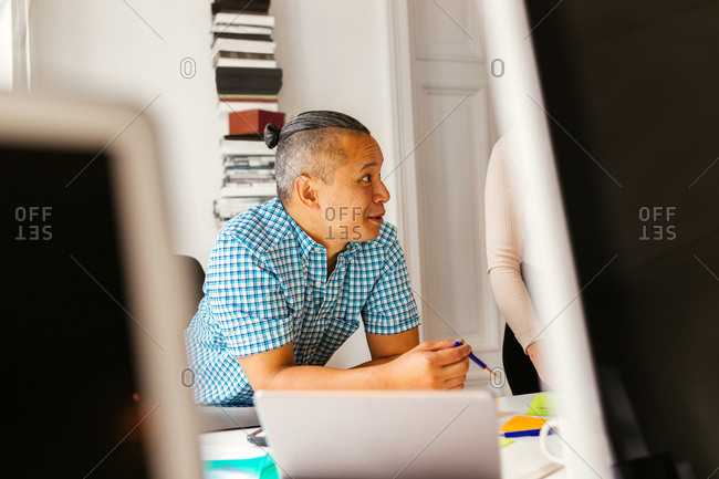 Editor leaning on desk in office