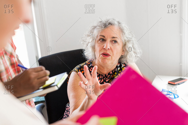 Woman leading business meeting, coworkers writing in notepad