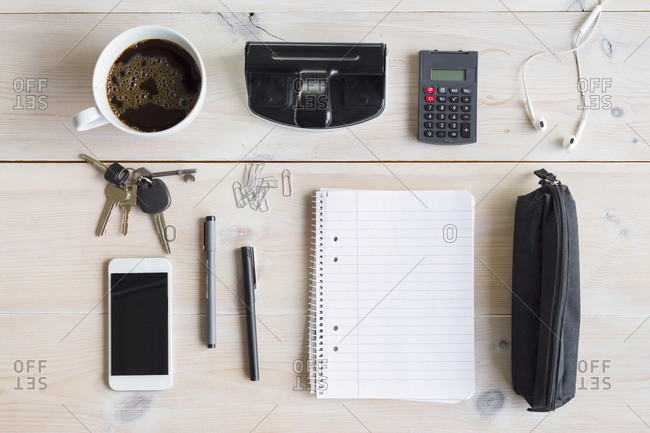 Office supplies, smart phone, keys and coffee cup on desk