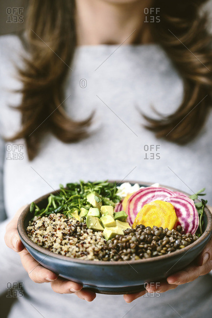 A woman wearing a gray shirt is holding an abundance bowl made up of quinoa, sprouts, lentils, avocados, and chioggia beets