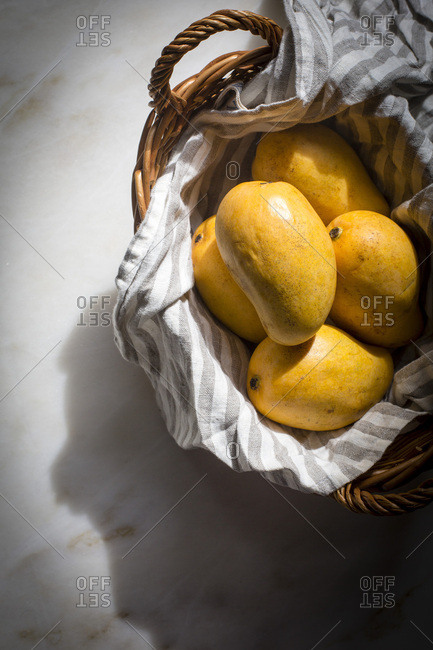 Mangoes in a basket on a marble table on top down shot