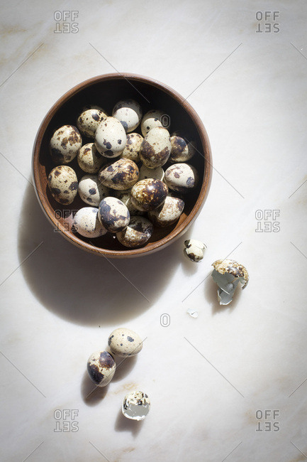 Quail eggs in a wooden bowl with broken shells on the side on a marble backdrop on top view