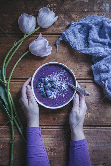 Woman eating a blueberry smoothie bowl on a rustic wooden table