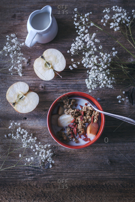 Granola with apples and oat milk served in a bowl
