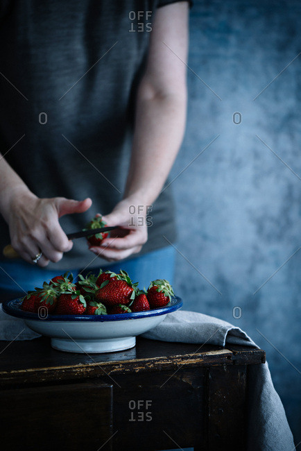 A woman slicing strawberries