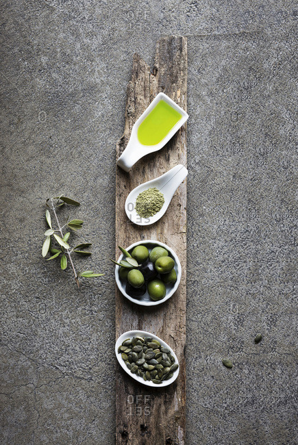 Green food: olive oil, macha tea, olives, pumpkin seed on grey background