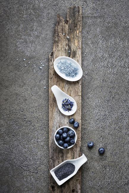 Blue food: blue salt, oolong blend tea, blueberries, poppy seeds on grey background
