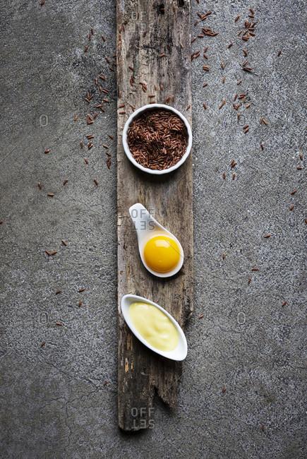 Yellow food: Thai red rice, egg yolk, mayonnaise on grey background