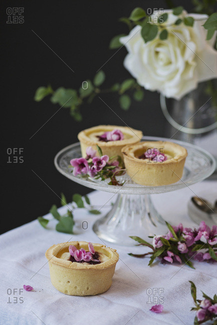 Ricotta cheese and jam tartlets on table with flowers