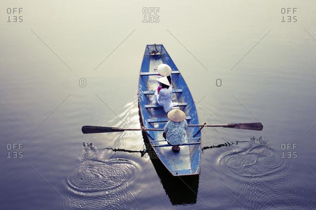 Vietnamese women wearing traditional costume, sitting on boat in lake